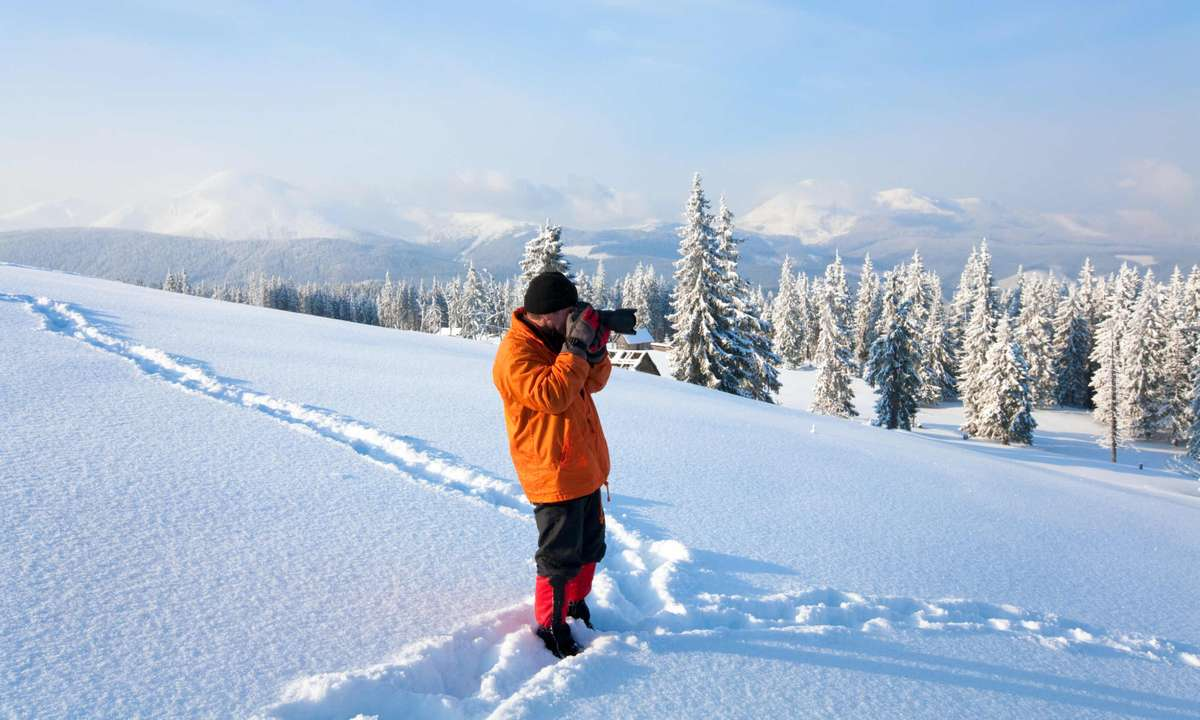A man photographs in ankle-deep snow (Dreamstime)
