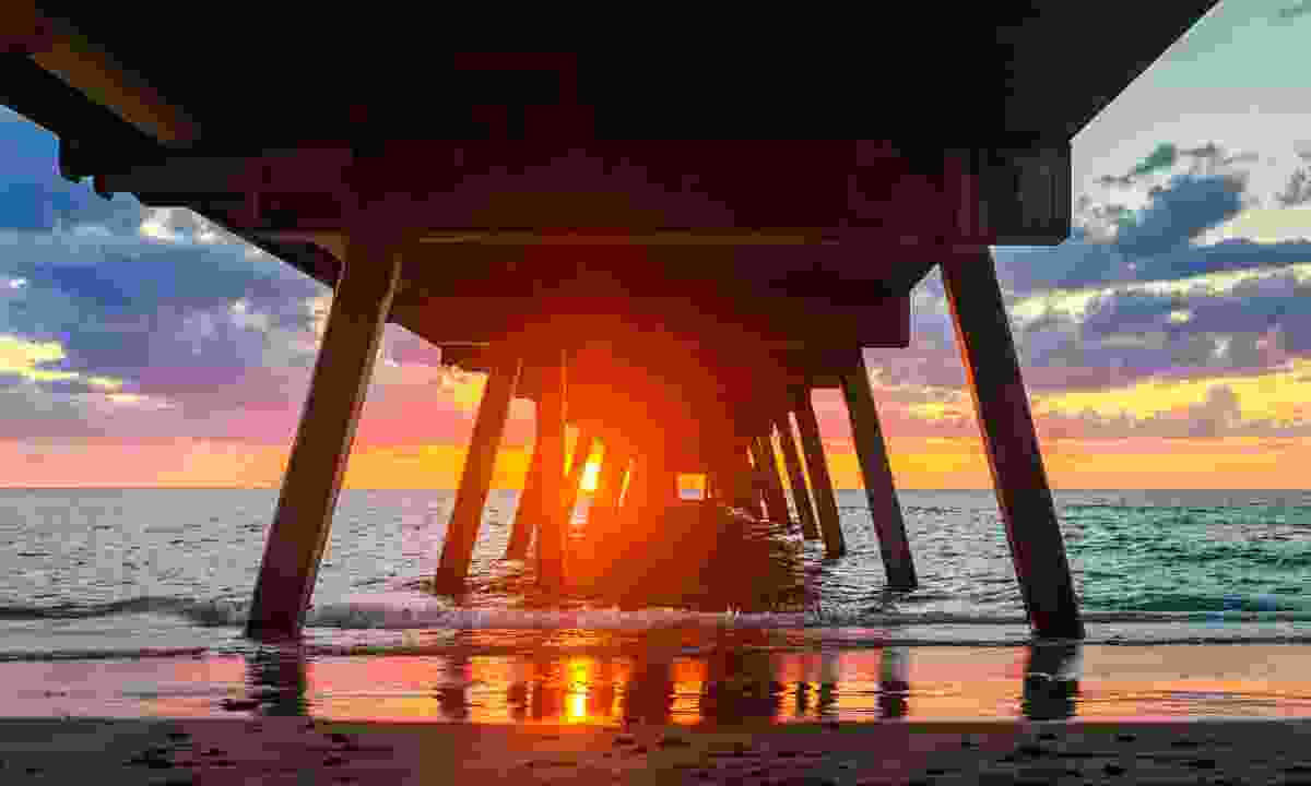 Sunset from under Glenelg jetty pylons (Dreamstime)