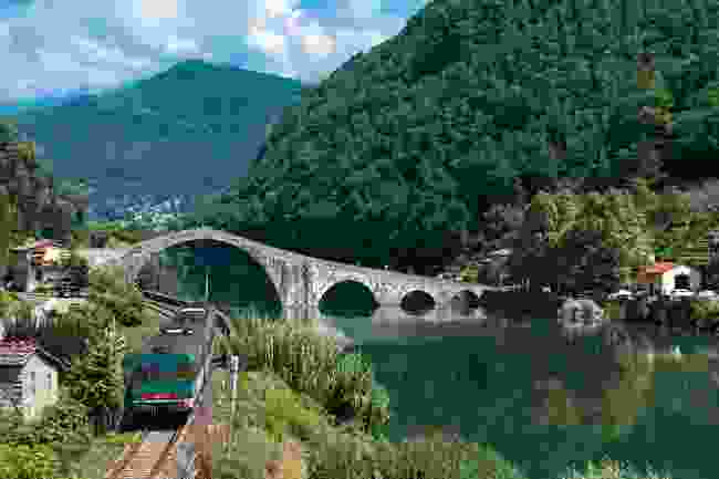 A train travels past the Devil's Bridge in Tuscany (Shutterstock)