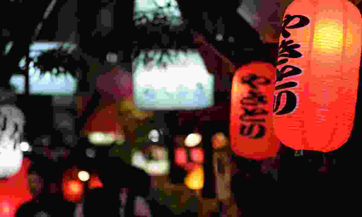 """Red paper lanterns advertising chicken skewers in a dark alley in Tokyo at night. The sign reads """"Yakitori"""" in Japanese (Shutterstock)"""