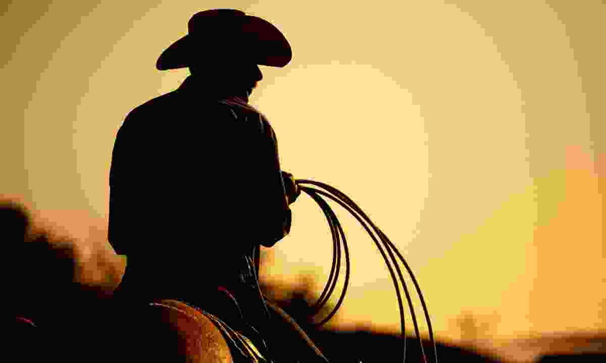 Cowboy riding into the sunset (Dreamstime)
