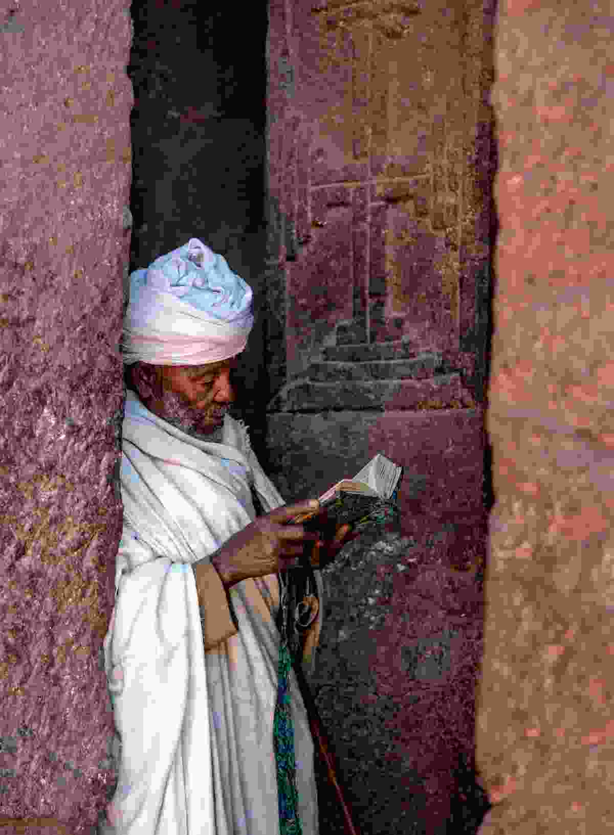A priest reads his prayer book on the west porch of Bete Maryam in Lalibela (Nigel Pavitt)