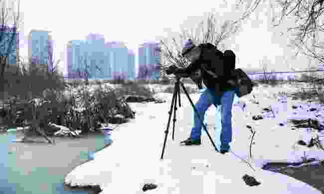 A photographer keeps equipment in a bag, while photographing in the snow (Dreamstime)