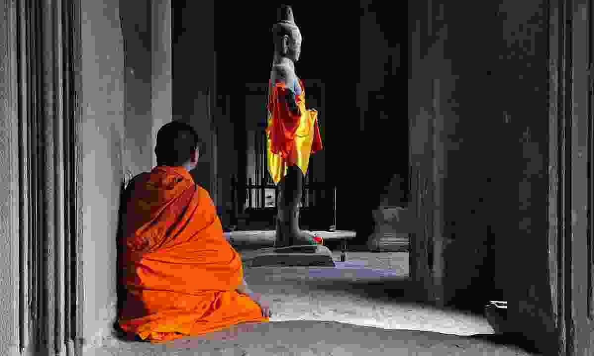 Monk admiring statue in Angkor Wat (Dreamstime)