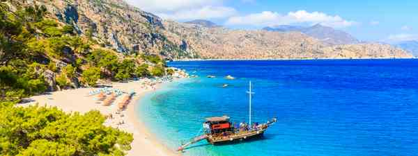 Boat anchoring on beautiful Apella Beach, Karpathos island (Shutterstock)