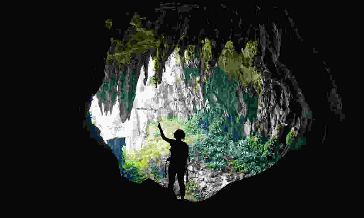 Exploring a cave in Borneo (Dreamstime)