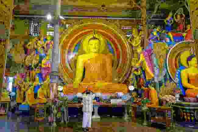 A man praying in the Gangaramaya Temple (Shutterstock)