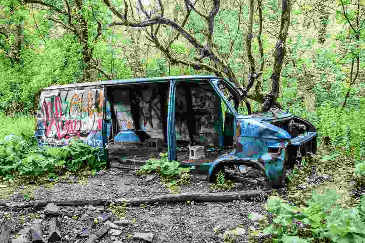 Junked vans, cars, and trucks lead to the old factory (Lisa Beard)