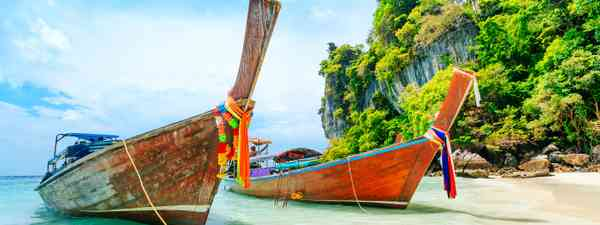Boats tied with rainbow-coloured ribbons on the shore of Phuket, Thailand (Shutterstock)