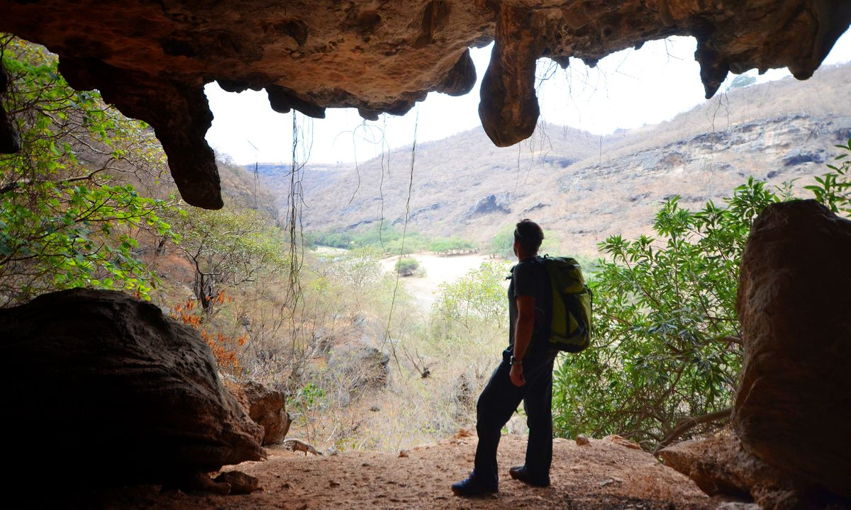 Justin gazes down Wadi Darbat from a dramatic overhanging limestone cave (Phoebe Smith)