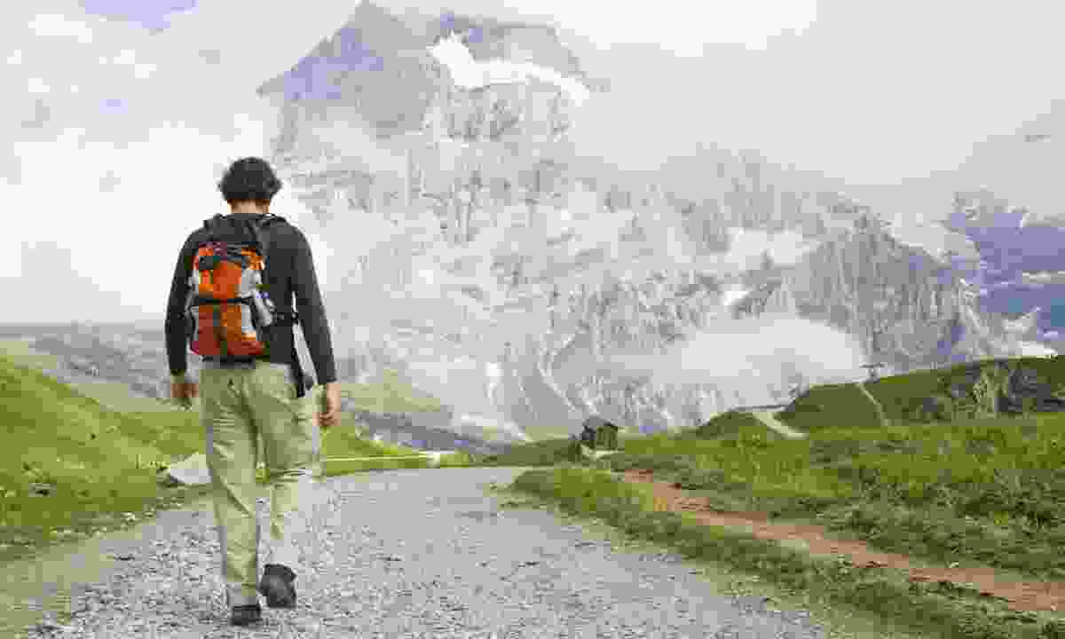 Young man walking in the Swiss Alps. (Dreamstime)