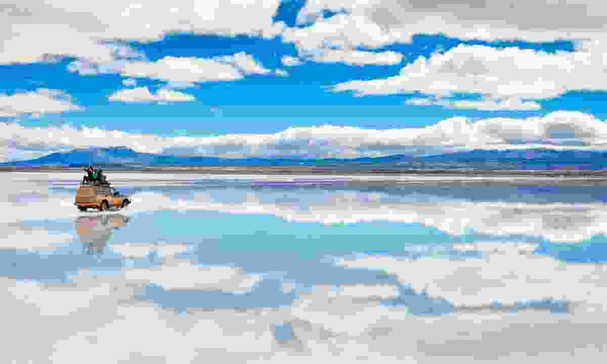 Tour vehicle on the mirror surface of Salar de Uyuni (Shutterstock)