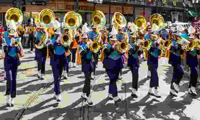 A marching band parades through the streets of New Orleans during Mardi Gras (Shutterstock)