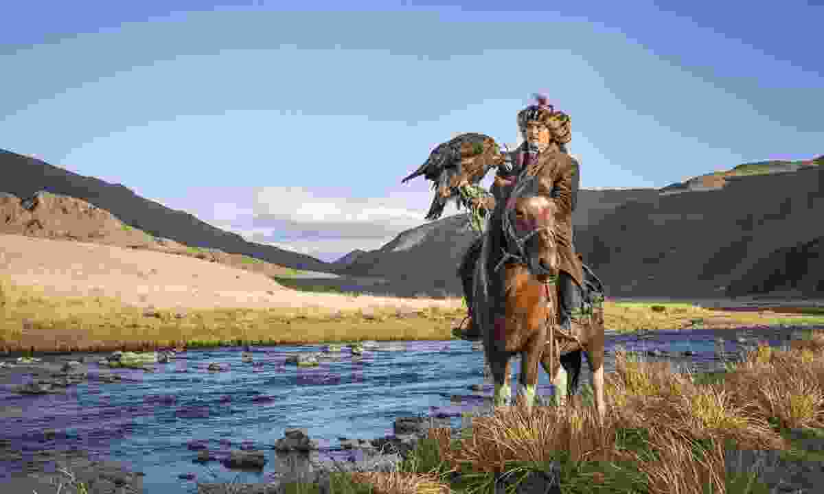 Mongolian nomad eagle hunter on his horse (Dreamstime)