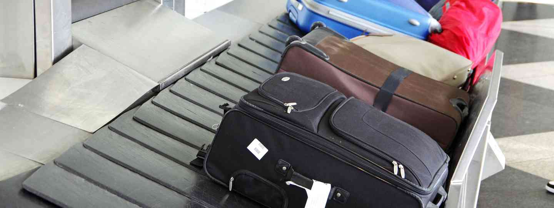 Suitcases on airport conveyor belt (Dreamstime)