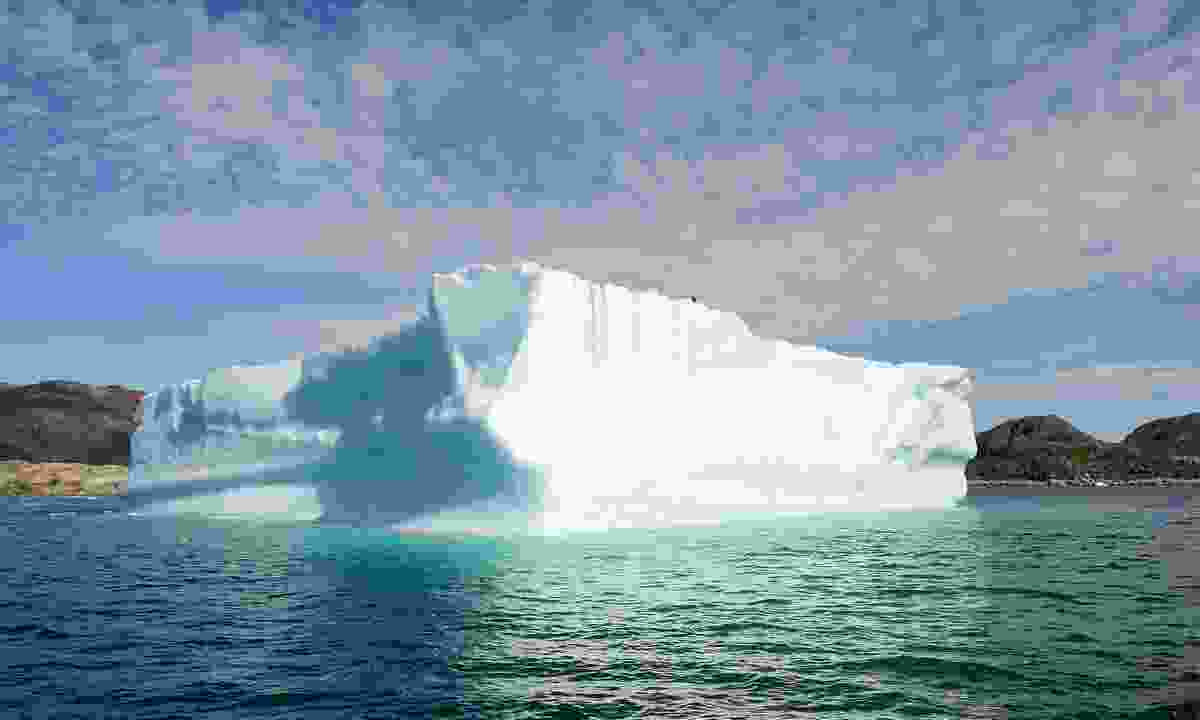 A giant iceberg floating past Uuunartoq (Dreamstime)