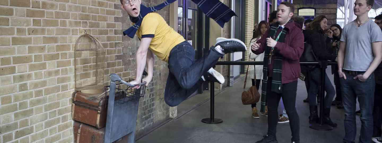 Harry Potter fan posing at Platform 9¾ (Dreamstime)