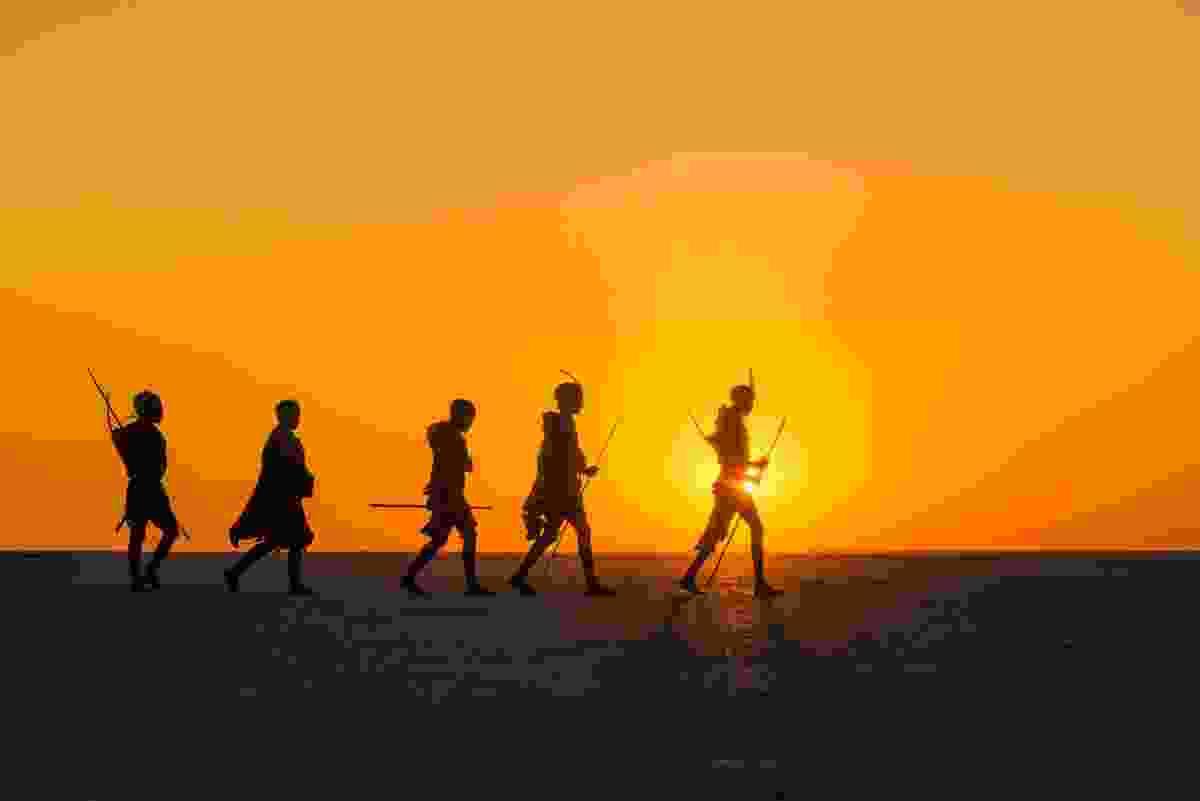 Bushmen walking across salt pan, Makgadikgadi Pans, Botswana (Frans Lanting)
