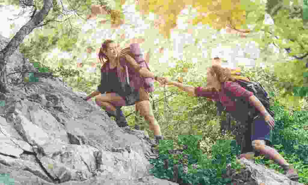 Lending a hand to a fellow traveller to help to climb a mountain (Dreamstime)