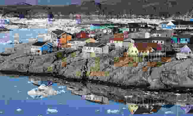 The colourful houses of Ilulissat reflected on the water (Dreamstime)