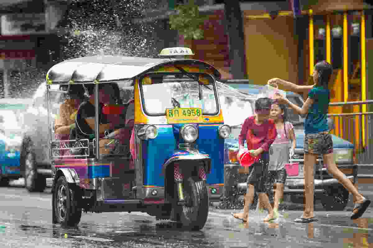 Children splashing people inside a tuk-tuk. You've been warned (Shutterstock)