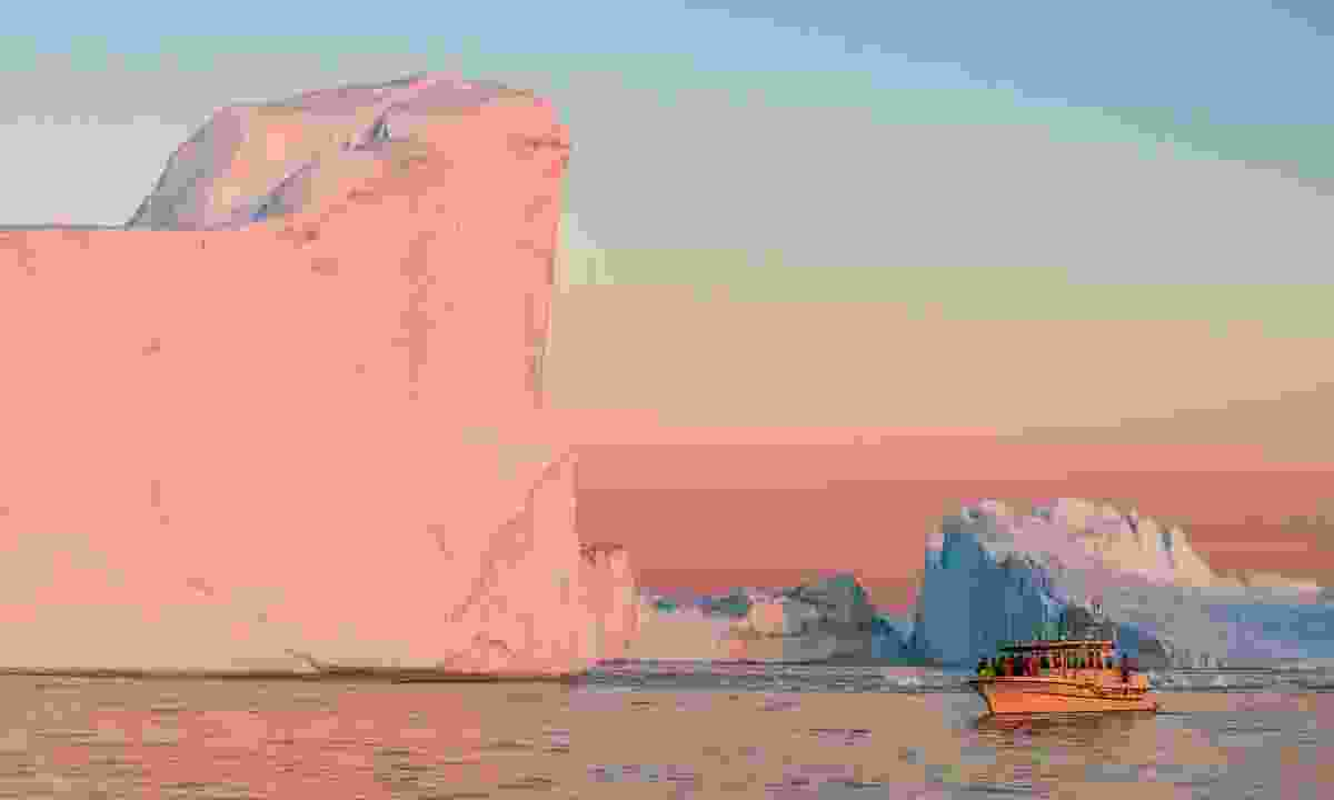 A giant iceberg reflects a pinky-glow from the midnight sun (Dreamstime)