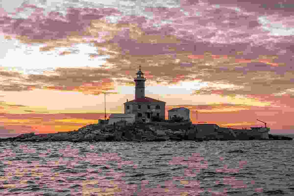 The sun sets over a lighthouse in Rovinj, Croatia (Shutterstock)