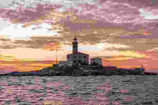 The sun sets over a lighthouse in Rovinj, Croatia (Shutterstock)
