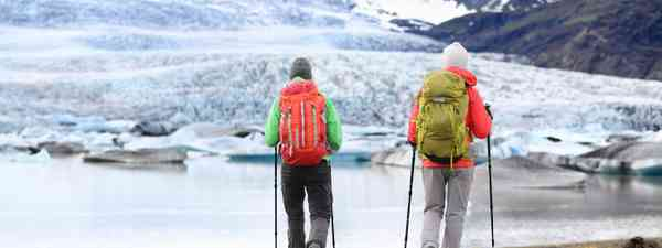 Two travellers using their walking poles on an Arctic hike (Shutterstock)