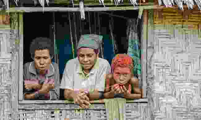 Family watching from their hut in PNG (Shutterstock)