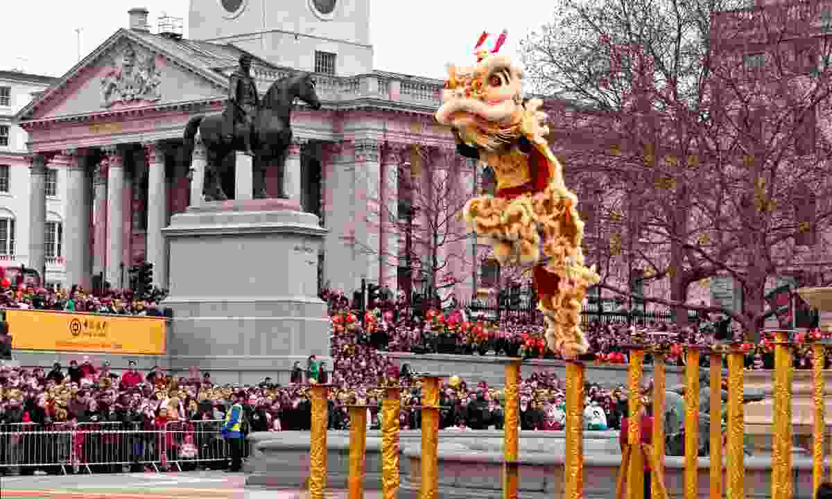 Lion Dancers leap across the poles in Trafalgar Square (Shutterstock)