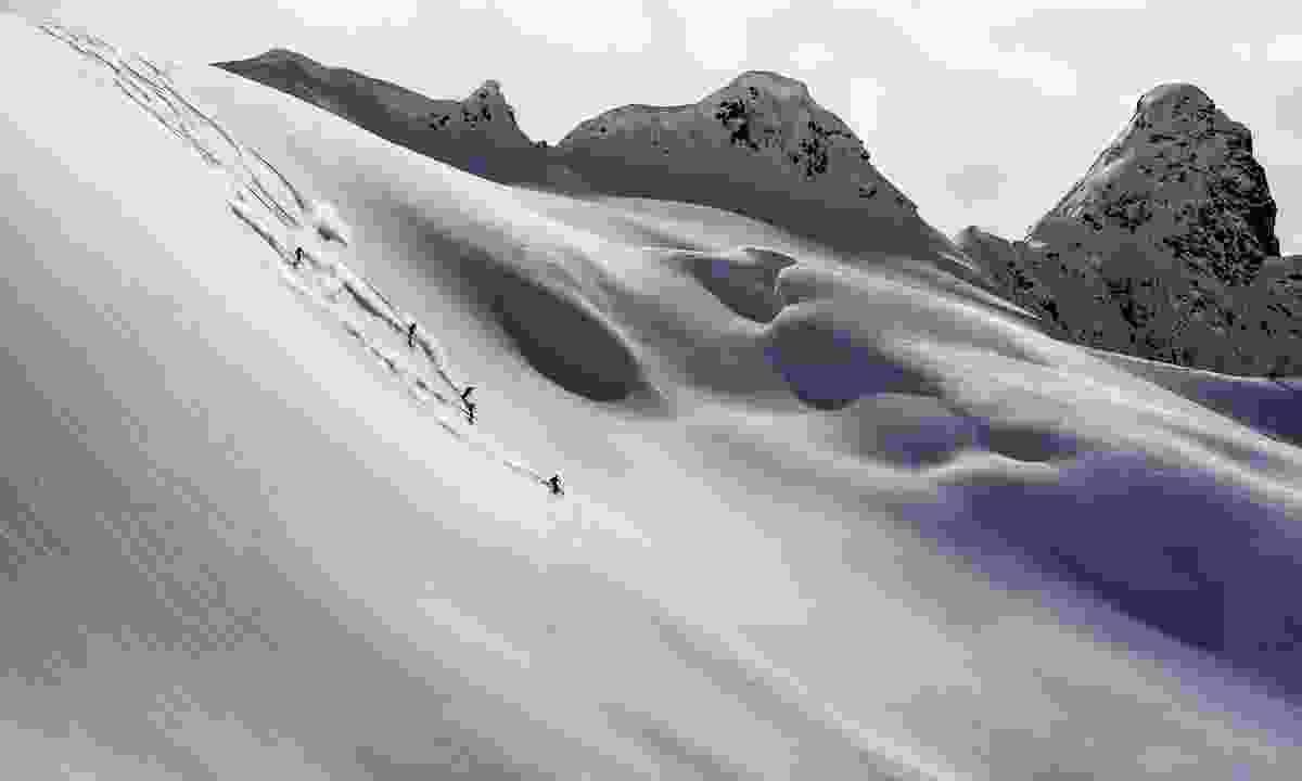 Heli-skiers descending on a slope near Mica Heli Skiing Lodge (Destination BC/Blake Jorgenson)