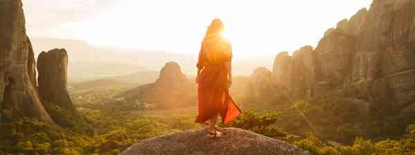 Girl admiring rocks formation as sun sets (Dreamstime)