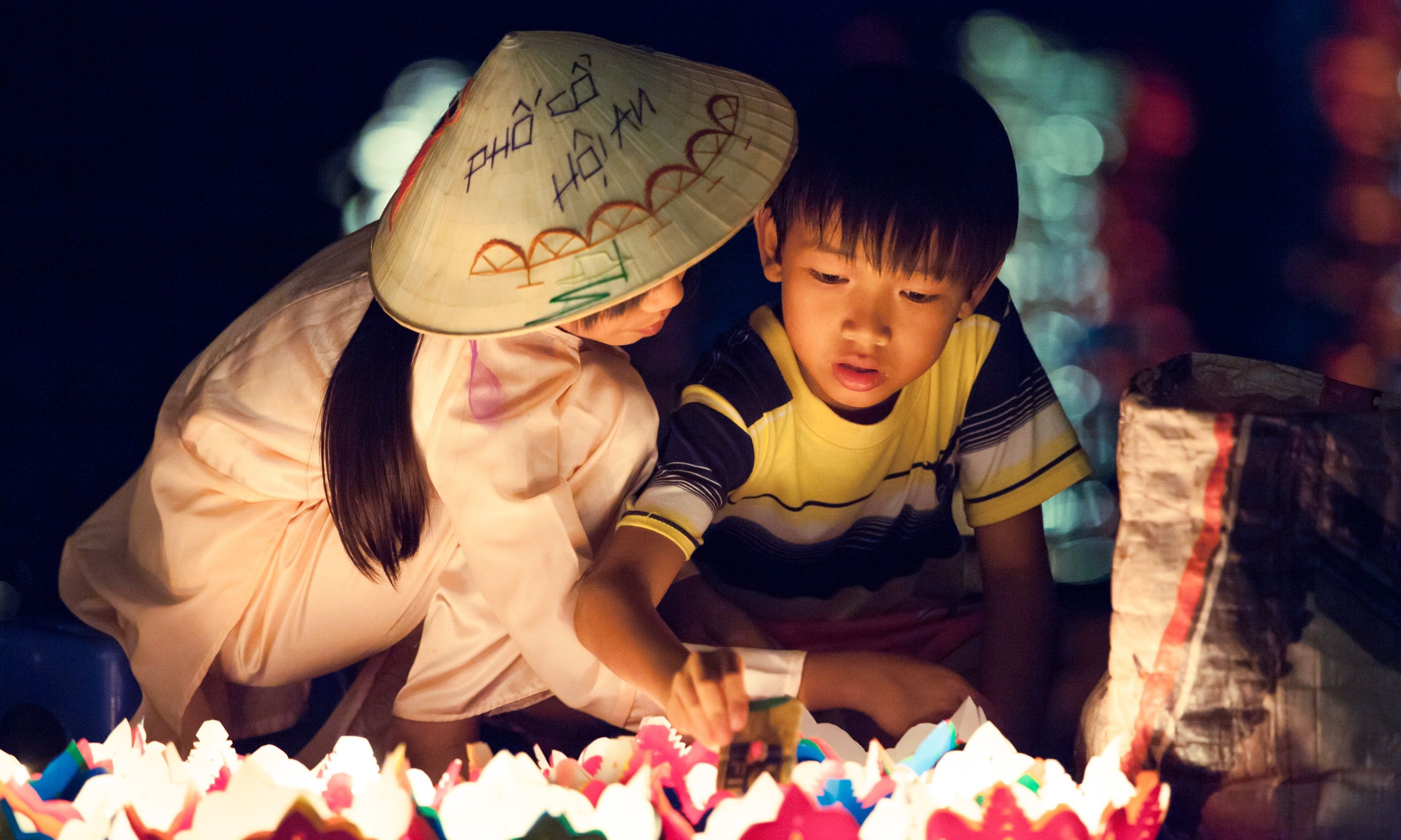 Kids lighting lanterns (Shutterstock.com)