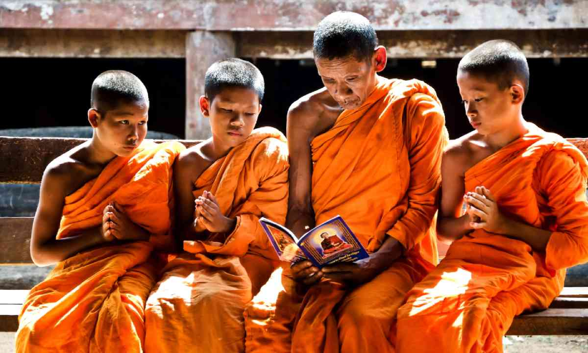 A monk teaches young novice monks, Thailand (Shutterstock)