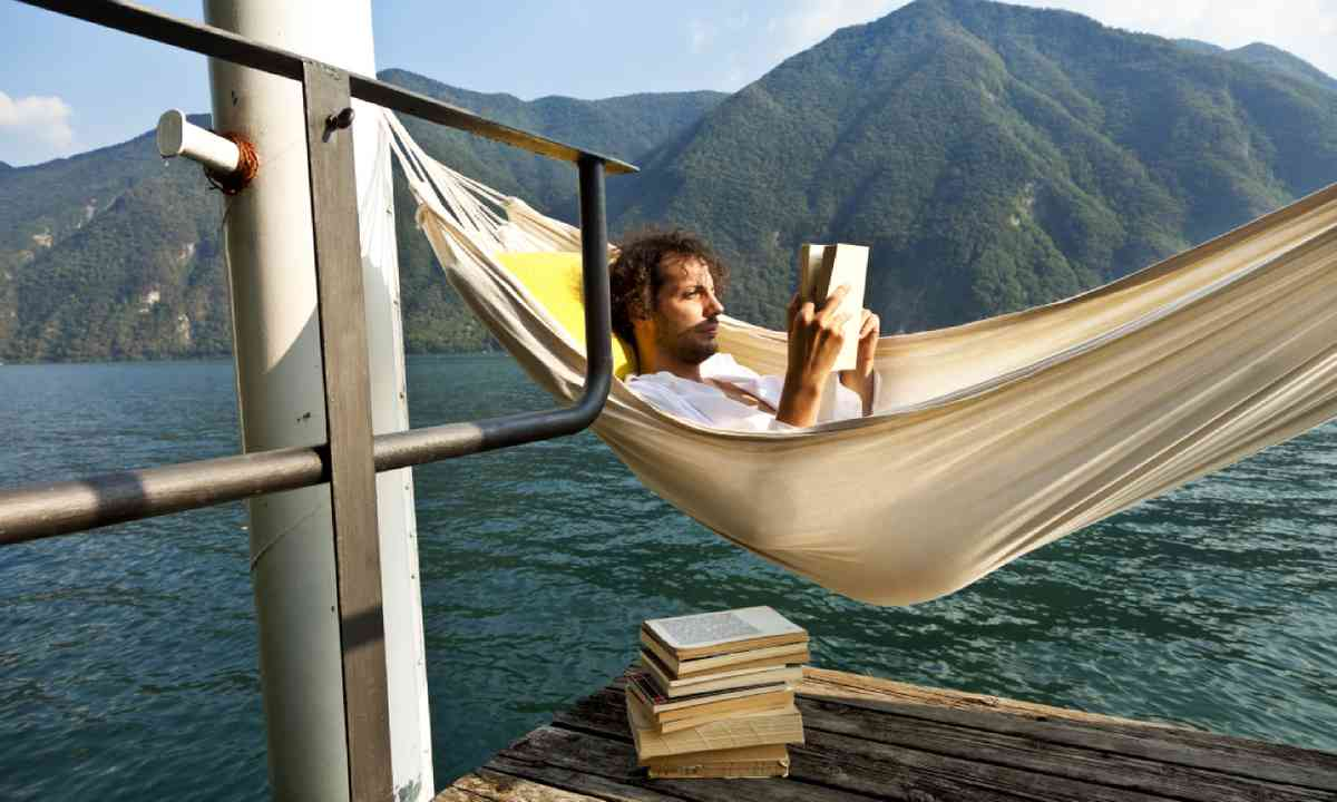 Reading on a lake dock (Shutterstock)
