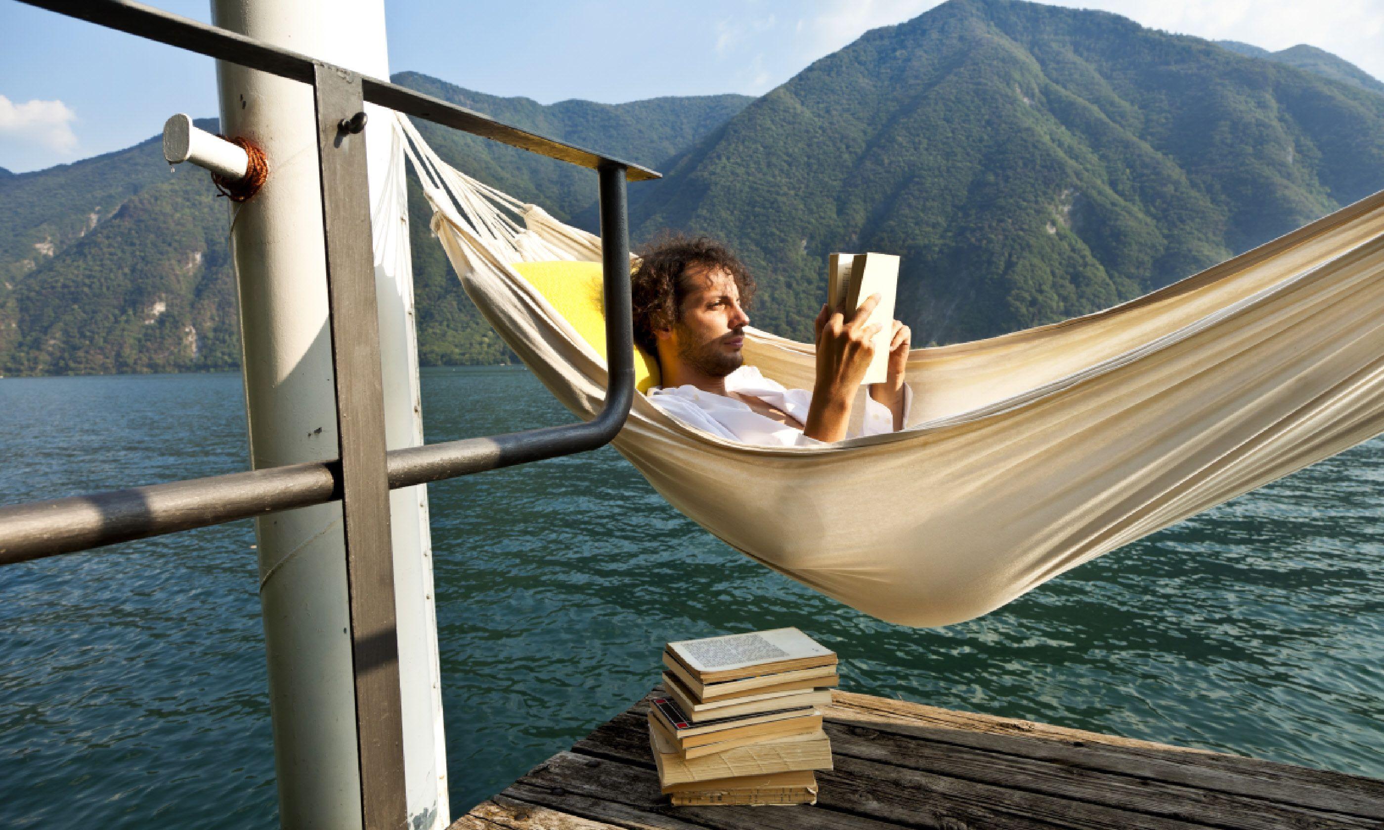 Reading on a lake dock (Shutterstock)