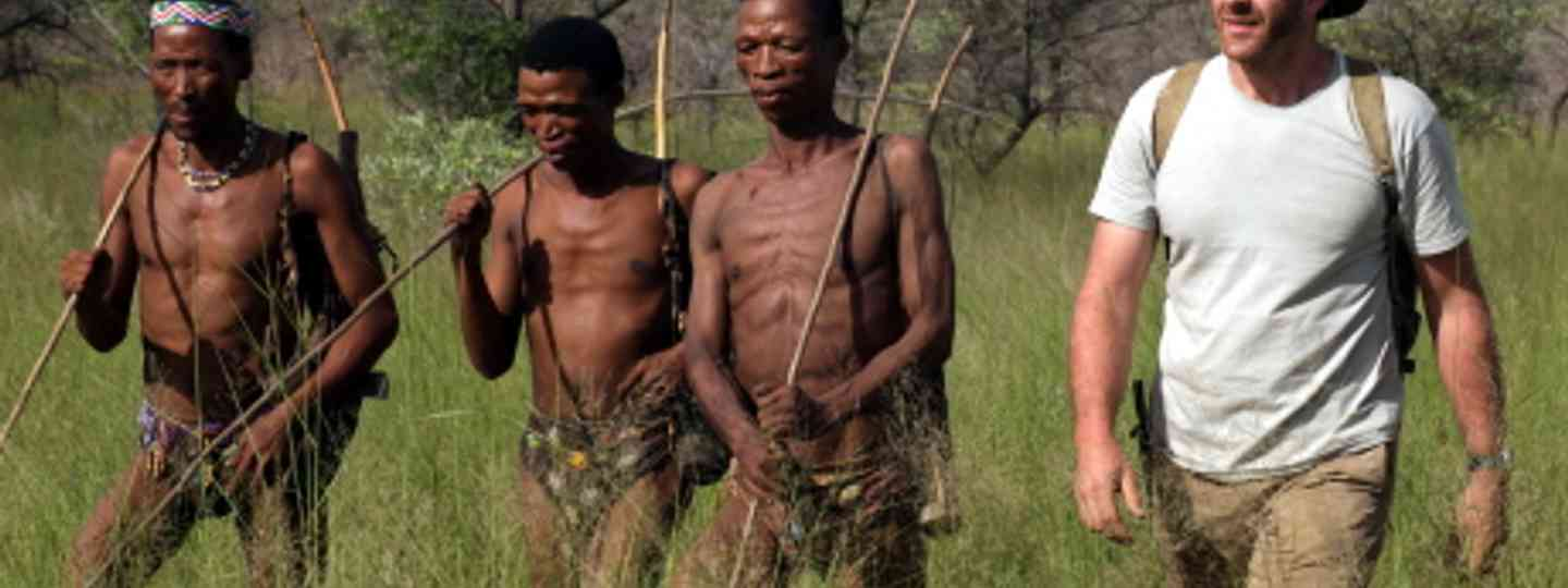 Guy Grieve walking through long grass with San Bushmen hunters (Laura Coates, Icon Films)