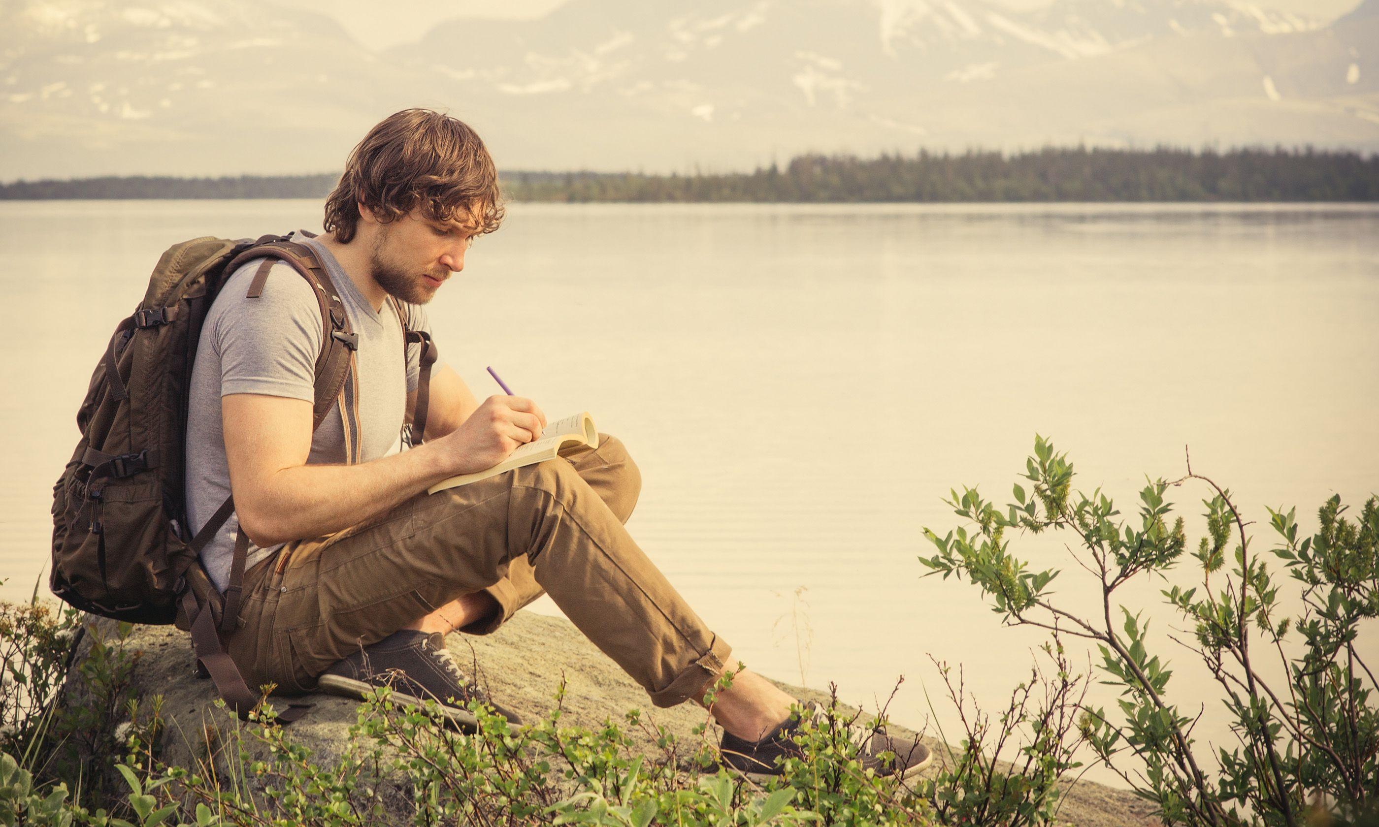 Backpacker writing in journal (Shutterstock.com)