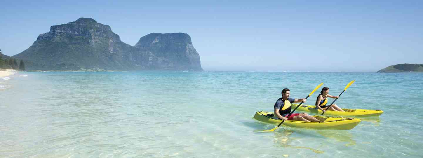 Couple kayaking by Lagoon Beach on Lord Howe Island (Destination NSW)