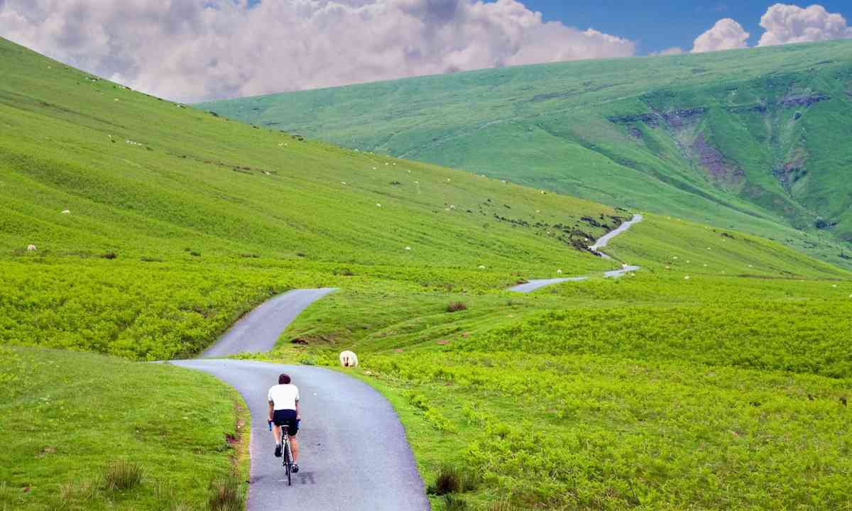 Cyclist riding through green hills (Shutterstock.com)