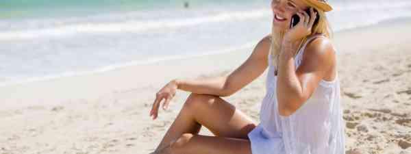 Woman talking on phone on beach (Shutterstock: see credit below)