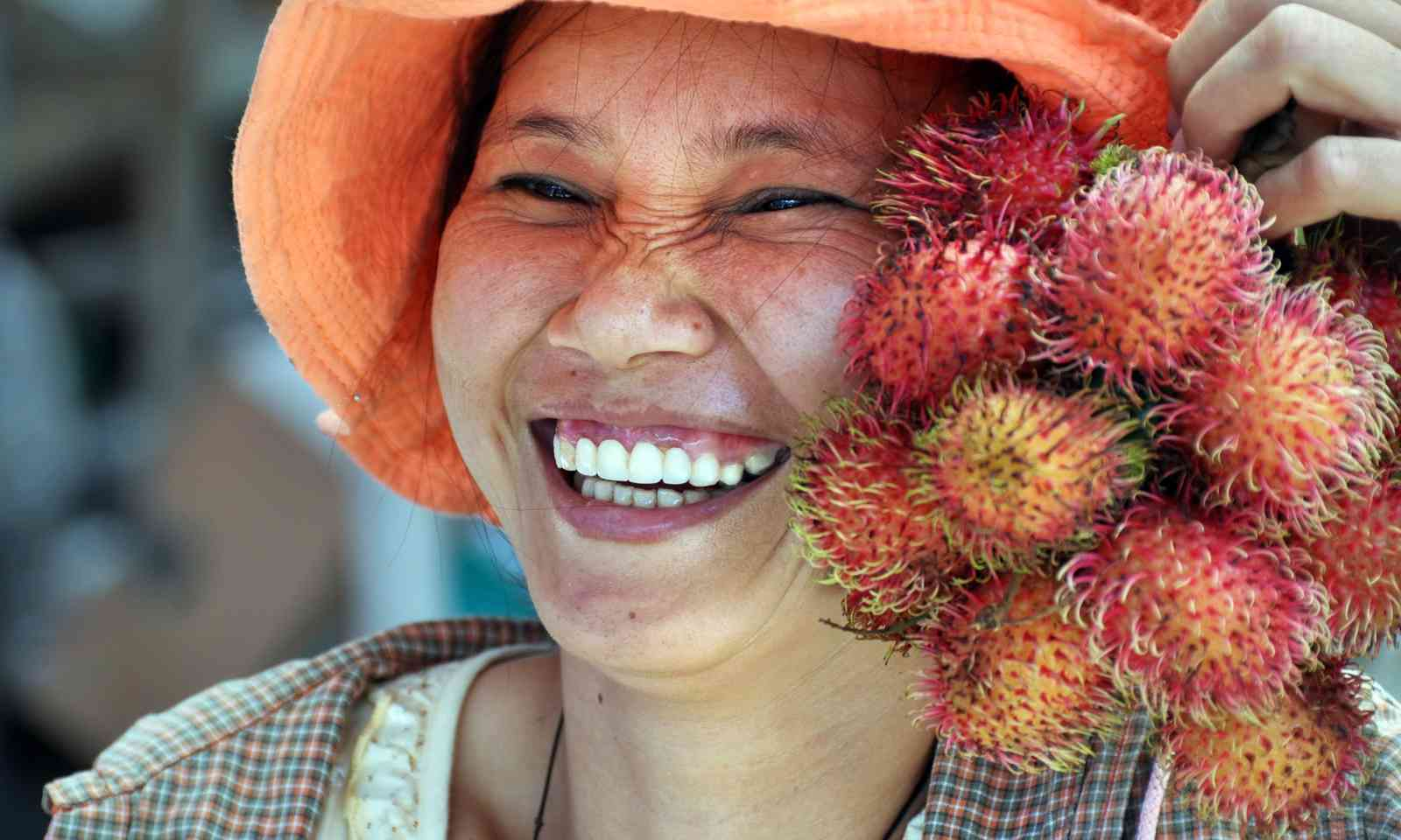 Tour guide with lychees (Dreamstime)