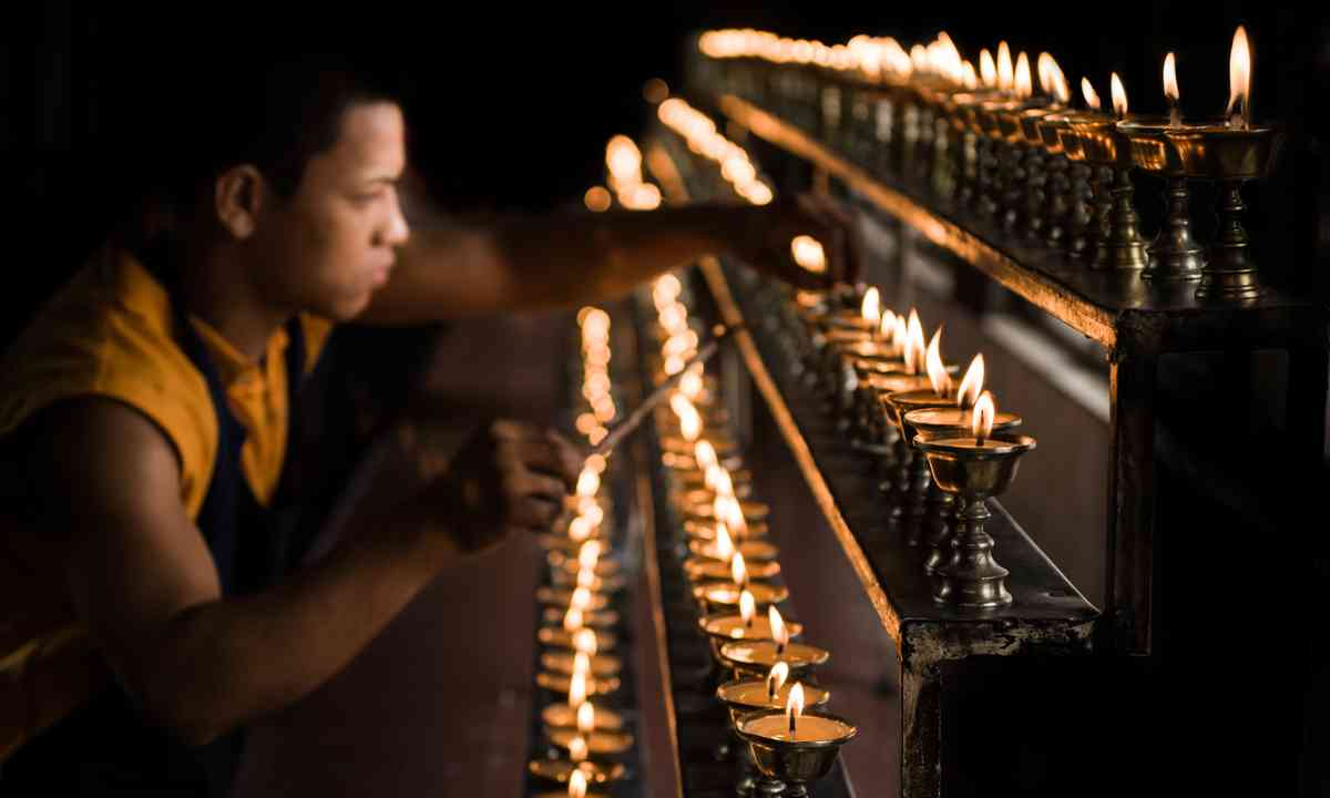 Monk with candles (Shutterstock.com)
