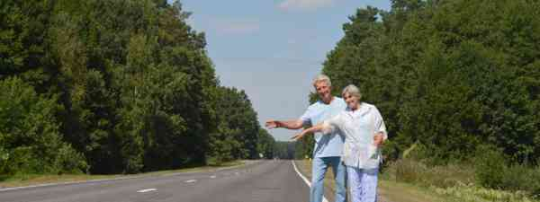 Elderly couple hitchhiking (Shutterstock)