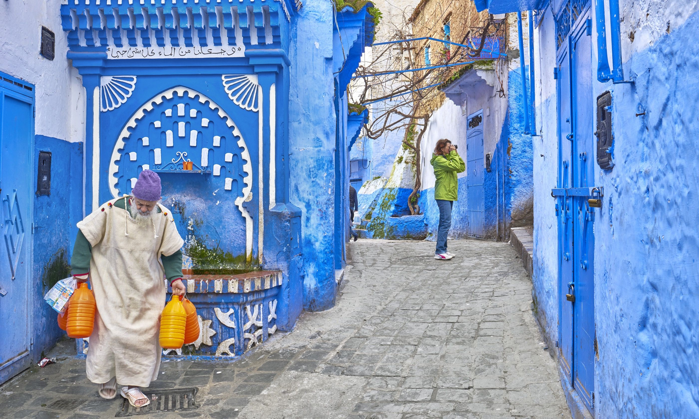 Local man carrying water from well, Chefchaouen (Shutterstock.com)