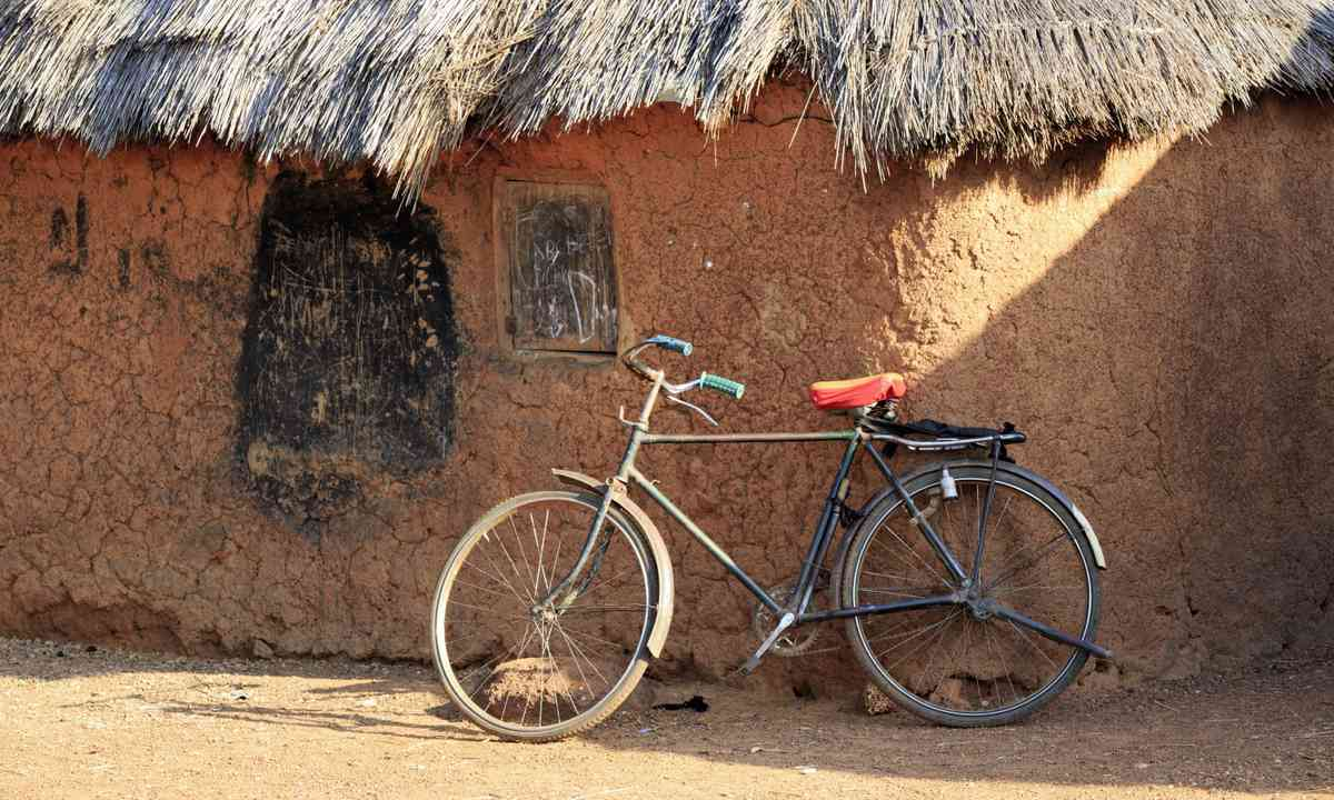 Bicycle leaning against mud hut (Dreamstime)