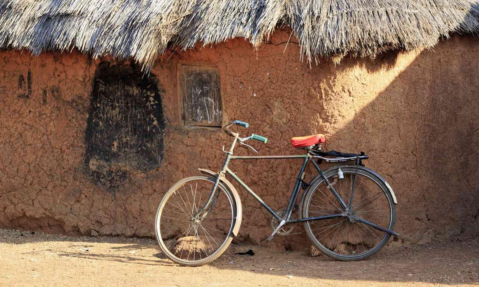 Bicycle leaning against mud hut (Dreamstime)
