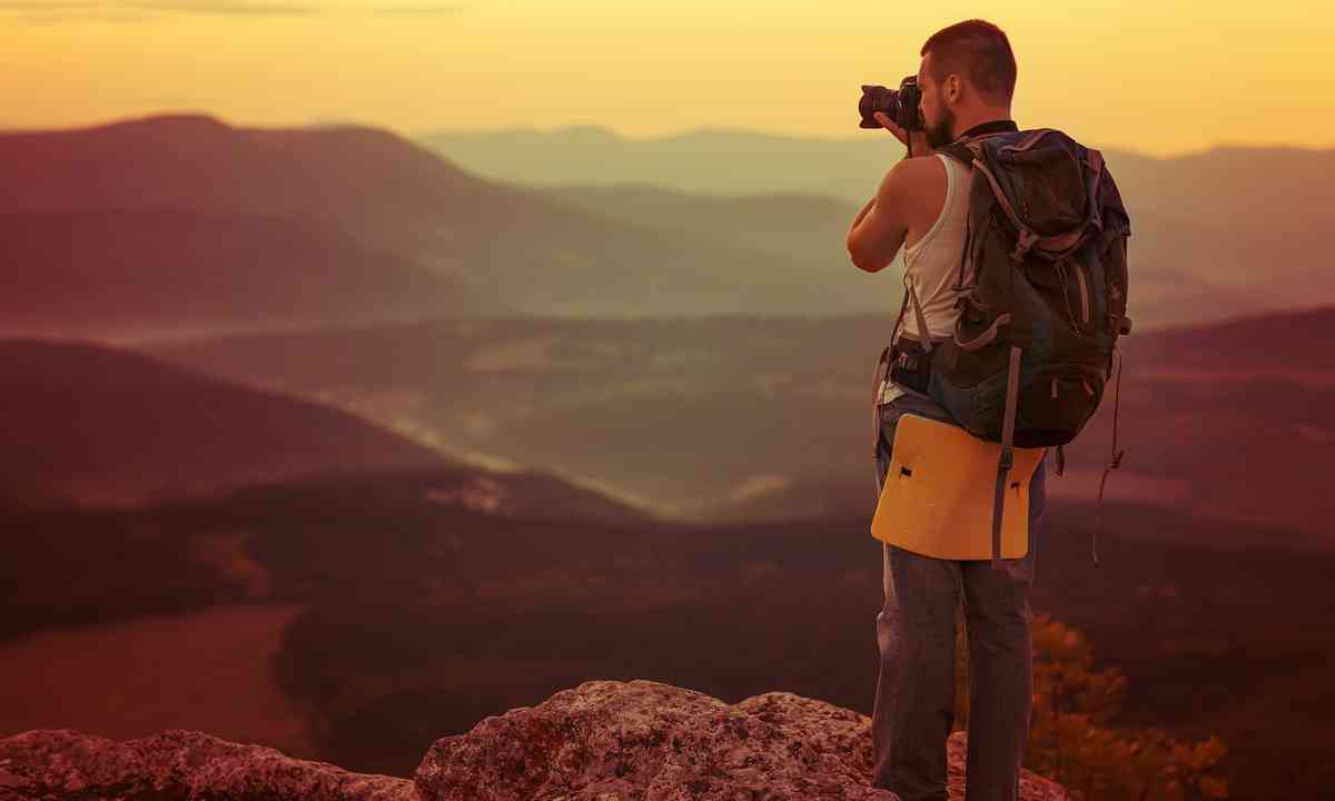 Guy taking landscape photos (Shutterstock.com)