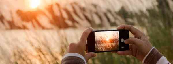 Person filming sunset with iPhone (Dreamstime)